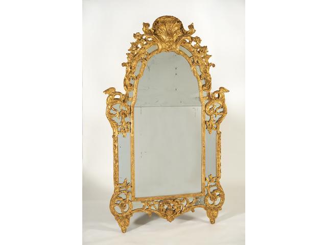 Haut et large miroir en bois doré. La partie haute richement sculptée